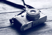 Retro camera on wooden table in shades of grey, closeup — Stock Photo