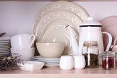 Kitchen utensils and tableware on shelf — Stockfoto