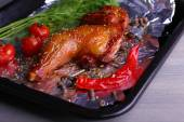 Smoked chicken leg with cherry tomatoes on pan on table close up — Stock Photo