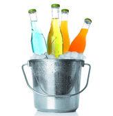Flessen van smakelijke drank in de metalen emmer met ijs geïsoleerd op wit — Stockfoto