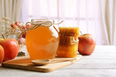 Delizioso miele con la mela sulla tabella su sfondo chiaro — Foto Stock