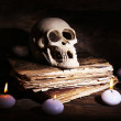 Still life with human skull, retro book and candlelight in dark on wooden table, closeup — Stock Photo #68852203