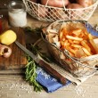 Tasty french fries and fresh potatoes in metal baskets on wooden table background — Stock Photo #68856003