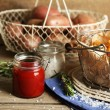 Tasty french fries and fresh potatoes in metal baskets on wooden table background — Stock Photo #68856091