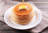 Delicious pancakes with honey on plate on table close-up — Stock Photo