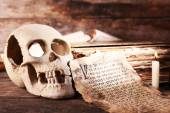 Still life with human skull, retro book and quill on wooden table, closeup — Stock Photo