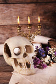 Still life with human skull and candlelight on wooden table, closeup — Stock Photo