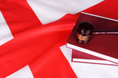 Wooden gavel and books on England flag background — Stock Photo