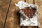 Bar of chocolate in foil on wooden background — Stock fotografie
