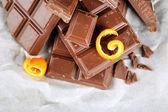 Chocolate with orange peels on parchment, closeup — Stock Photo