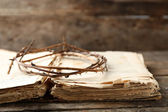 Crown of thorns and bible on old wooden background — Stock Photo