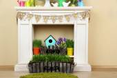 Fireplace with beautiful spring decorations in room — Stock Photo
