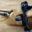 Wine bottle wrapped in burlap cloth on wooden planks background — Stock Photo #69146637