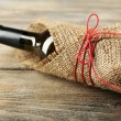 Wine bottle wrapped in burlap cloth on wooden planks background — Stock Photo #69146669