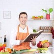 Man with recipe book in hands at table with different products and utensil in kitchen on white wall background — Stockfoto #69196615