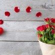 Red roses wrapped in paper with hearts on wooden table background — Stock Photo #69197159