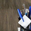 Pens in metal holder on wooden table background — Stock Photo #69199043