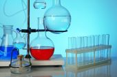 Fixed laboratory glassware on support on colorful background — Stock Photo