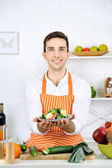 Man at table with different products and utensil in kitchen on white wall background — Stock Photo