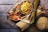 Different types of pasta on sackcloth on wooden background — Stock Photo
