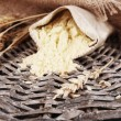 Whole flour in bag with wheat ears on wicker mat, closeup — Stock Photo #69206025