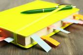Notebook with bookmarks on wooden table — Стоковое фото