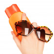 Bottle of suntan cream and sunglasses in female hands isolated on white — Stock Photo #69251453