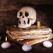 Still life with human skull, retro book and candlelight on wooden table, closeup — Stock Photo #69254003