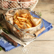 Tasty french fries and fresh potatoes in metal baskets on wooden table background — Stock Photo #69255241