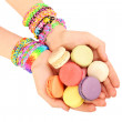 Female hands with bracelets and pile of macaroons isolated on white — Stock Photo #69256005