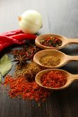Different kinds of spices in spoons, close-up, on wooden background — Stock Photo