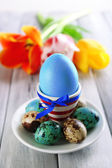 Easter egg in holder and tulips — Stock Photo