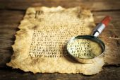 Grunge paper with hieroglyphics with magnifier on wooden background — Zdjęcie stockowe