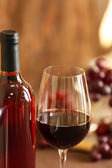 Bottle and glass of rose wine with grape on blurred background — Stock Photo