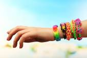 Female hand with bracelets on color blurred background — Stock Photo