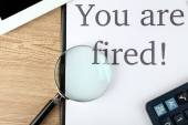 Message You're Fired on clipboard on wooden table, closeup — Stockfoto