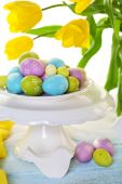 Easter eggs on vase and tulips — Stock Photo