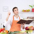 Man with recipe book in hands at table with different products and utensil in kitchen on white wall background — Stockfoto #69297245