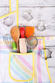 Set of kitchen utensils in pocket of apron on wooden background — Stock Photo