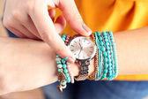 Stylish bracelets and clock on female hand top view — Stock Photo