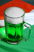 Glass of green beer on Ireland flag background — Stock Photo