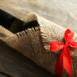 Wine bottle wrapped in burlap cloth on wooden planks background — Stock Photo #69354001