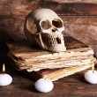 Still life with human skull, retro book and candlelight on wooden table, closeup — Stock Photo #69355489