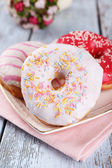 Delicious donuts with icing on plate on wooden background — Стоковое фото