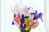 Beautiful bouquet of spring flowers in glass vase on curtain background — Stock Photo