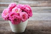 Beautiful pink roses in pot on wooden background — Stock Photo