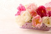 Bouquet of fresh tulips in wicker tray on light background — Stock Photo