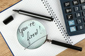 Message You're Fired on notebook with calculator, marker and magnifying glass on wooden table, closeup — Stock Photo