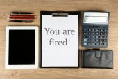 Message You're Fired on clipboard on wooden table, top view — Stock Photo