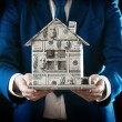 Model of house made of money in male hands on black background — Stock Photo #69385885